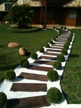 Caminho de pedras com degraus em madeira ao redor de um jardim.