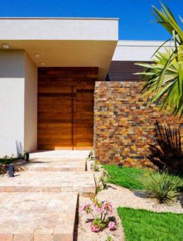 Fachada rústica de casa com muro em pedras mosaico e paredes com madeira.