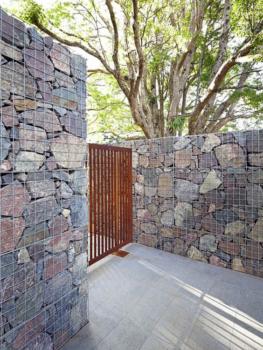 Entrada de casa com dois muros decorados com capote em blocos e um portão rústico no meio.